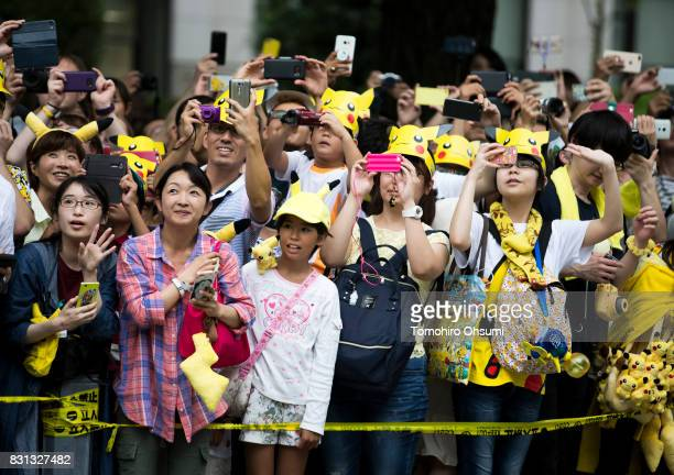 People look at performers dressed as Pikachu a character from Pokemon series game titles during a parade held as part of the Pikachu Outbreak event...