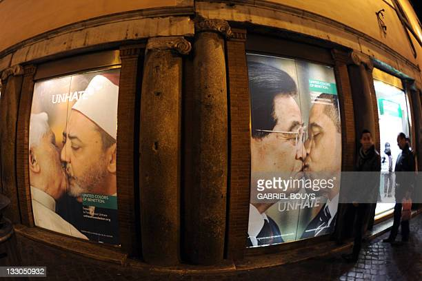 People look at photo montages of a new ad campaign of Italian clothing company Benetton in their shop in front of the Trevi fountain in Rome on...
