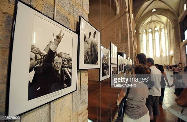 People look at photographs taken by Goksin Sipahioglu the Turkish photographer and founder of French photo agency Sipa Press shown during the 'Visa...