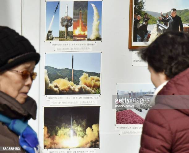 People look at photos of ballistic missiles in front of the North Korean Embassy in Beijing on Nov 29 2017 Pyongyang testlaunched an intercontinental...