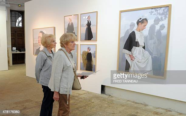 People look at pictures by French photographer Charles Freger during an exhibition on traditional costumes and headdresses in Brittany on June 20...
