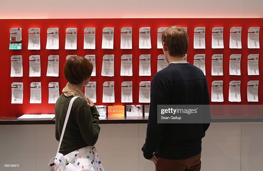 People look at pieces of paper with job openings from technoogy companies at the 2013 CeBIT technology trade fair on March 5, 2013 in Hanover, Germany. CeBIT will be open March 5-9.