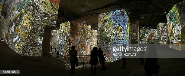 People look at projections of images of paintings by late French painter Marc Chagall during the exhibition 'Chagall Songes d'une nuit d'Été' at the...