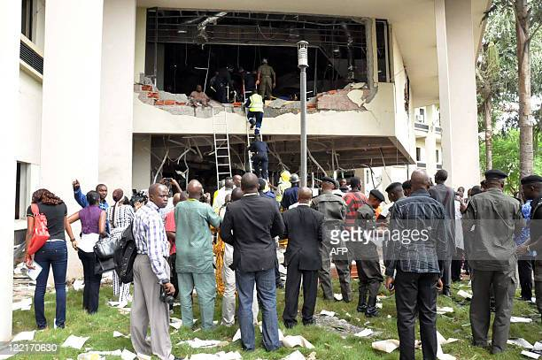 People look at rescue teams working in the debris of the United Nations House in Abuja on August 26 2011 after it was hit by a bomb that killed at...