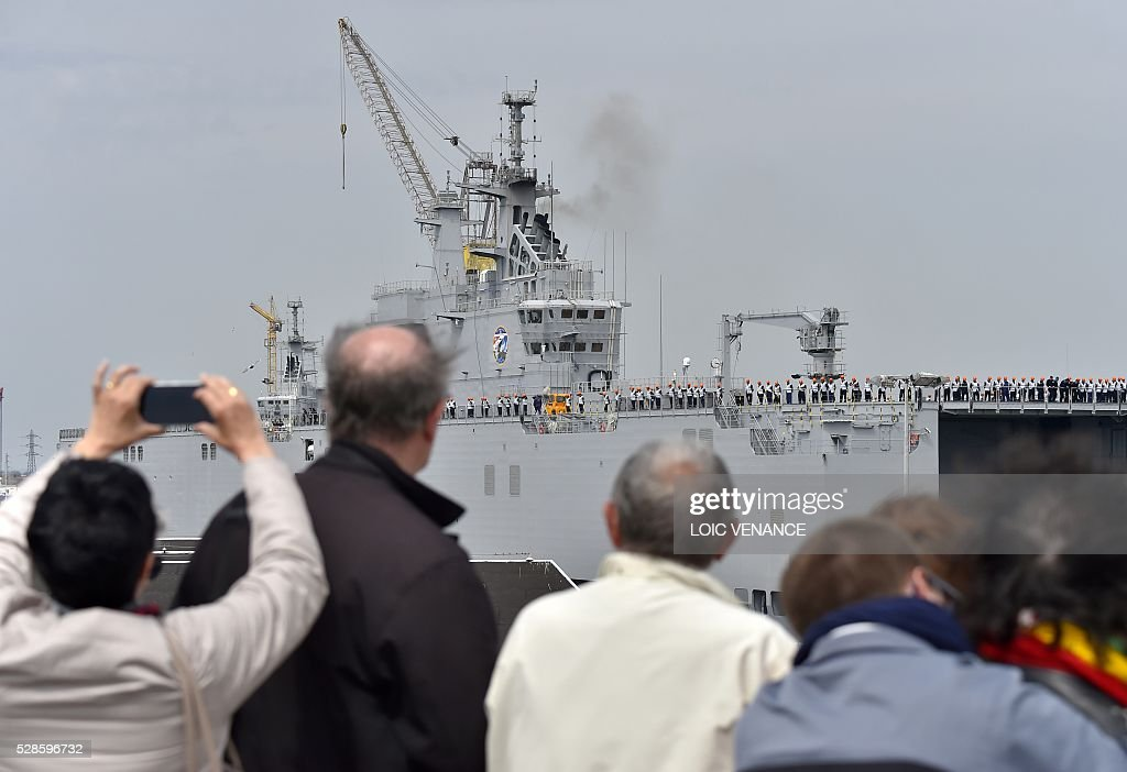 People look at sailors standing onboard the Gamal Abdl Nasser (ex-Vladivostok) Mistral class ship as they leave for a one week training session on May 6, 2016 in Saint-Nazaire, western France. The 'Nasser', first one of the two Mistral class ships sold by France to Egypt after its first sale cancellation to Russia, leaves Saint-Nazaire (Loire-Atlantique) on Friday for a week of Egyptian crew training at sea. / AFP / LOIC