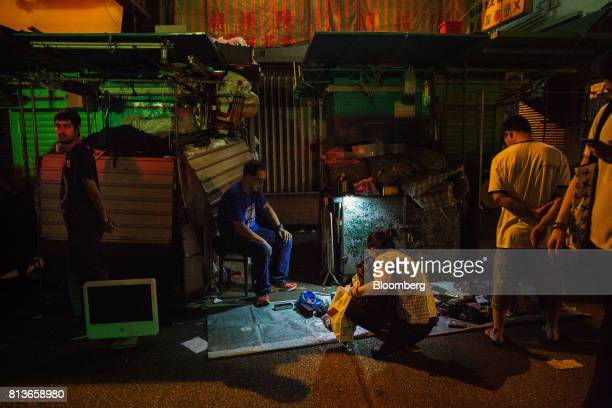 People look at scrap items for sale at a street stall at night in the Sham Shui Po district of Hong Kong China on Thursday May 18 2017 Sham Shui Po...