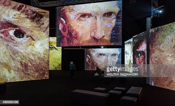 People look at screens displaying part of a painting by Dutch artist Vincent Van Gogh during the official opening of the 'Van Gogh Alive' multimedia...