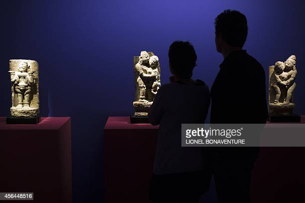 People look at sculptures as they visit the exhibition The KamaSutra spirituality and erotism in Indian art at the Paris' pinacotheque on October 1...