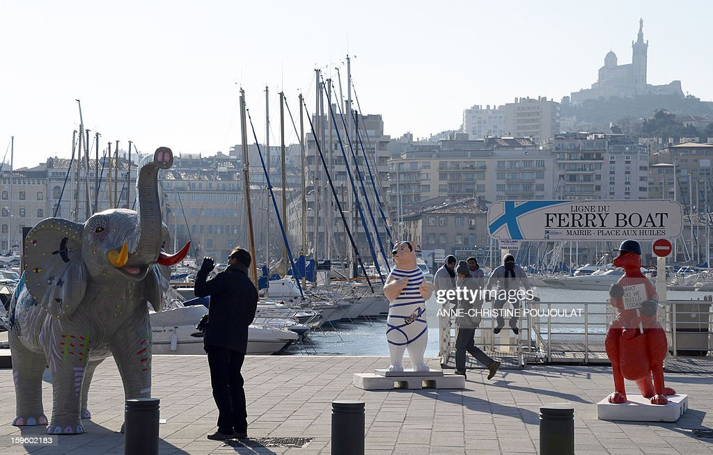 People look at sculptures of animals displayed at the Old Harbour on January 17, 2012 in Marseille during the Event 'FunnyZoo' Marseille-Provence 2013 European Capital of Culture. The event marks the start of a year, leading to a cultural renaissance in France's second-largest metropolitan area .