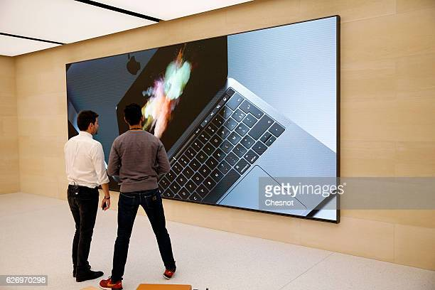 People look at the a signage for the new MacBook Pro laptop computer inside the new Apple store Saint Germain during the press day on December 01...