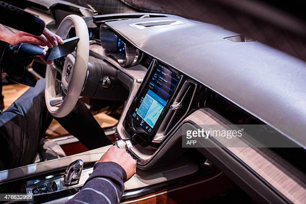 People look at the Apple digital technology onboard the Estate Vovlo concept car at the Volvo stand of the Geneva Motor Show on March 4 2014 AFP...