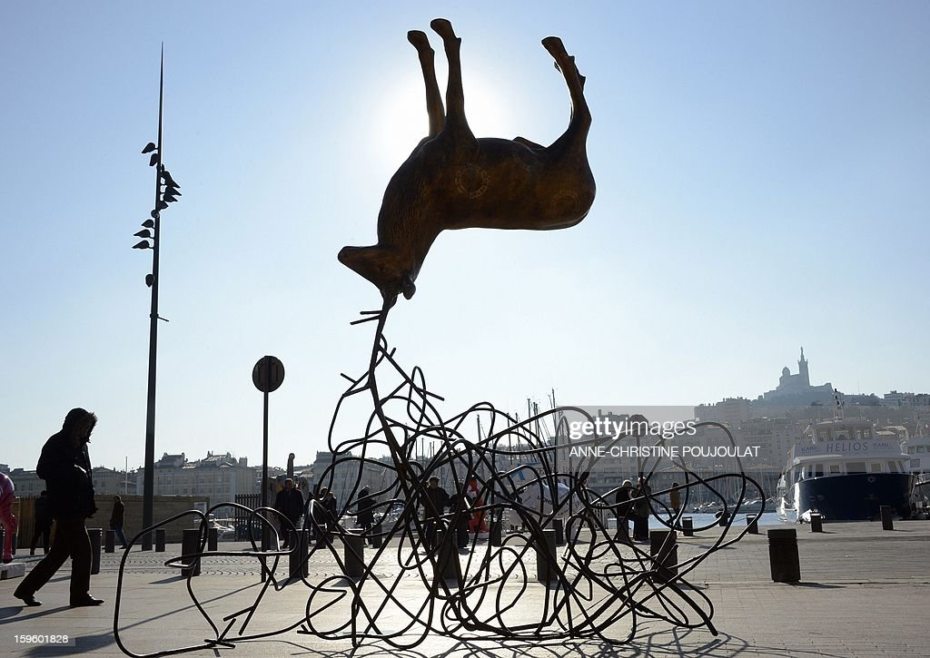 People look at the artwork 'Cerf/Frec' by the artist Luc Dubosc on the Old Harbour on January 17, 2012 in Marseille during the Event 'FunnyZoo' Marseille-Provence 2013 European Capital of Culture. The event marks the start of a year, leading to a cultural renaissance in France's second-largest metropolitan area .AFP PHOTO / ANNE-CHRISTINE POUJOULAT
