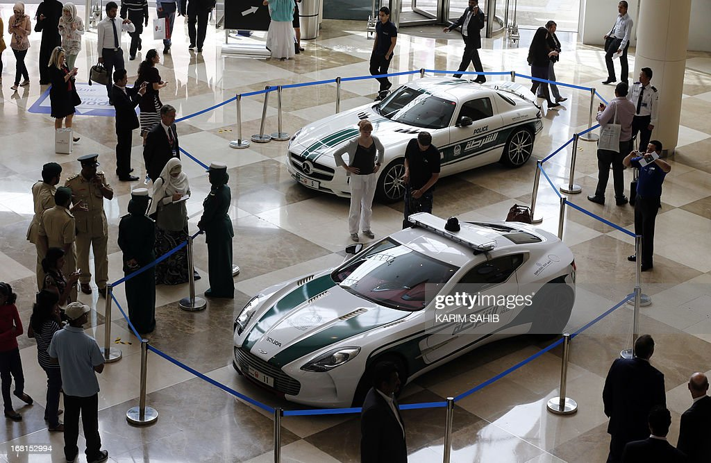 People look at the Aston Martin One-77 (front) and Mercedes SLS (back) on display during the Arabian Travel Market (ATM) at the Dubai World Trade Centre in the Emirati city on May 6, 2013. Dubai police have introduced top end sports cars to their patrol fleet to further strengthen the image of 'luxury and prosperity' of the Emirate.