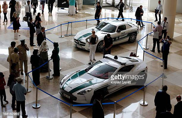 People look at the Aston Martin One77 and Mercedes SLS on display during the Arabian Travel Market at the Dubai World Trade Centre in the Emirati...
