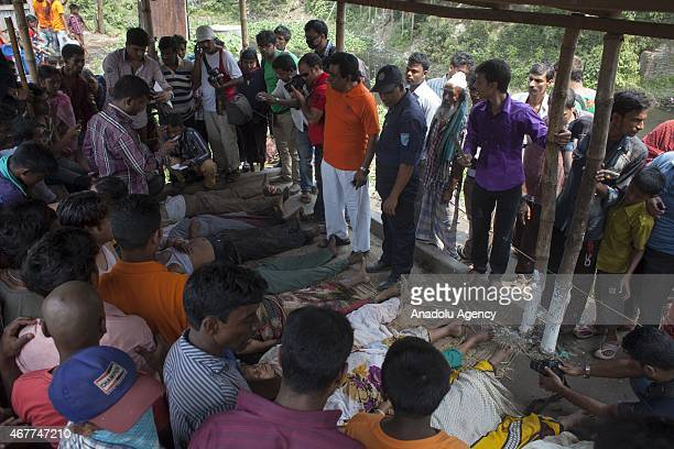 People look at the bodies of people who died in a stampede during the 'Astami Snan' the Hindu holy bath in the Old Brahmaputra River in Narayanganj...
