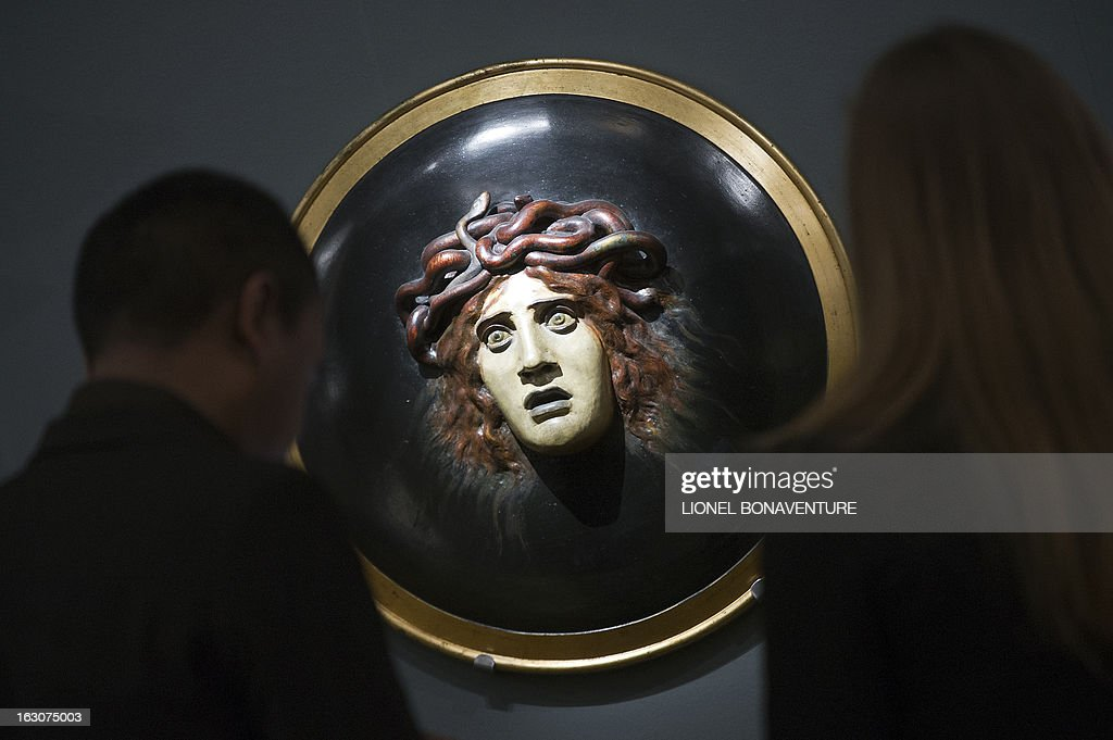 People look at the 'Bouclier avec le visage de meduse' by Arnold Bocklin during the exhibition 'The Angel of the Odd. Dark Romanticism from Goya to Max Ernst' at the Orsay museum in Paris, on March 4, 2013. The exhibition will run from March 5 until June 9, 2013.