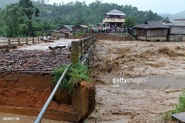 People look at the bridge which was washed away by the floodwaters in Thoubal District in Manipur state on August 1 2015 At least 21 people were...