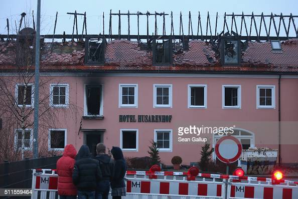 People look at the burntout remains of a former hotel that was to soon serve as a shelter for 300 asylum applicants following a fire in the early...