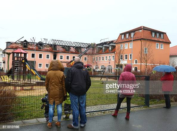 People look at the burntout roof truss of a former hotel that was under reconstruction to become a home for asylum seekers on February 21 2016 in...