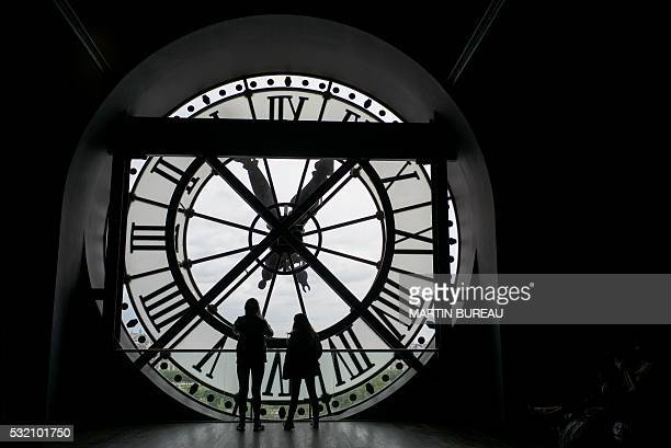People look at the city of Paris through one of the clocks of the Orsay museum on May 18 2016 / AFP / MARTIN BUREAU