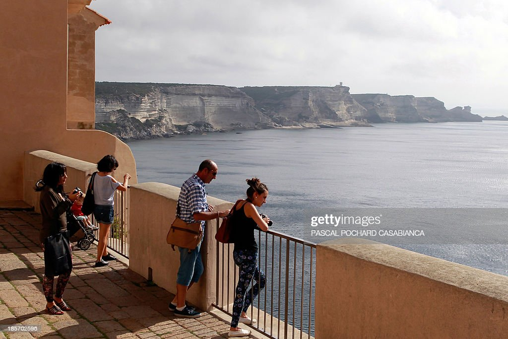 People look at the cliffs of the old city of Bonifacio, France's southern Mediterranean island of Corsica, on October 22, 2013. Bonifacio is classified as one of France's most beautiful villages. AFP PHOTO / PASCAL POCHARD-CASABIANCA