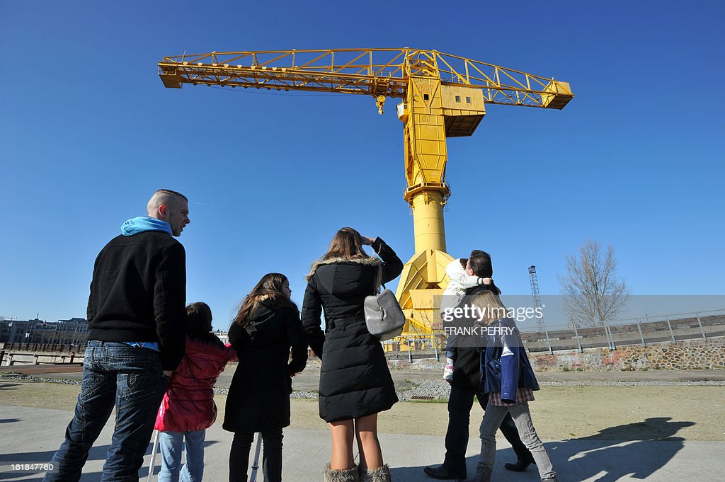 People look at the crane where Serge Charnay on February 17, 2013 spray painted the message ' Save our children from the justice' in Nantes on the third day of a protest on the 43 metre crane for his rights as a father. A second man yesterday climbed another crane in 'an act of solidarity' with Charnay, an action sanctioned by French association 'SOS Papa' indicating that the two men are' victims of family justice in France' .