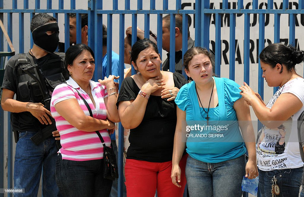 People look at the crime scene in which five people -- including a high school student -- were shot dead in the suburb of La Haya, in northern Tegucigalpa, on April 15, 2013. In March 2012, the UN announced Honduras had the world's highest murder rate, at 82.1 deaths per 100,000 people, while a local observatory on violence put the rate at 86.5 per 100,000. AFP PHOTO/Orlando SIERRA