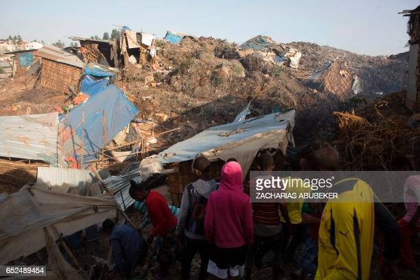 TOPSHOT People look at the damage done to dwellings built near the main landfill of Addis Ababa on the outskirts of the city on March 12 after a...