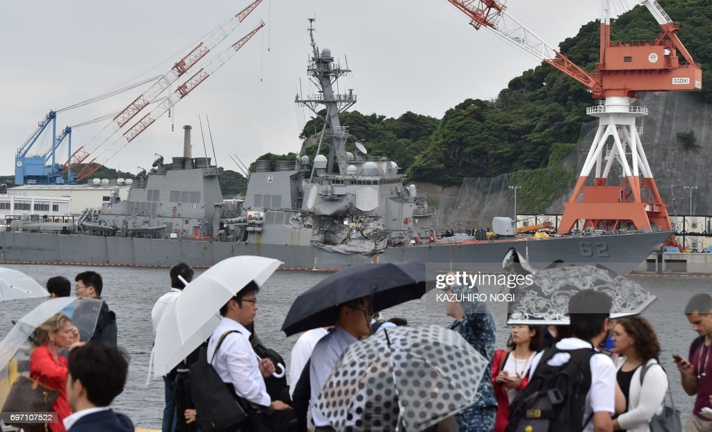 People look at the damages on the guided missile destroyer USS Fitzgerald at its mother port in Yokosuka, southwest of Tokyo on June 18, 2017. A number of missing American sailors have been found dead in flooded areas of a destroyer that collided with a container ship off Japan's coast, the US Navy said on June 18, 2017. / AFP PHOTO / Kazuhiro NOGI
