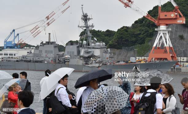 People look at the damages on the guided missile destroyer USS Fitzgerald at its mother port in Yokosuka southwest of Tokyo on June 18 2017 A number...