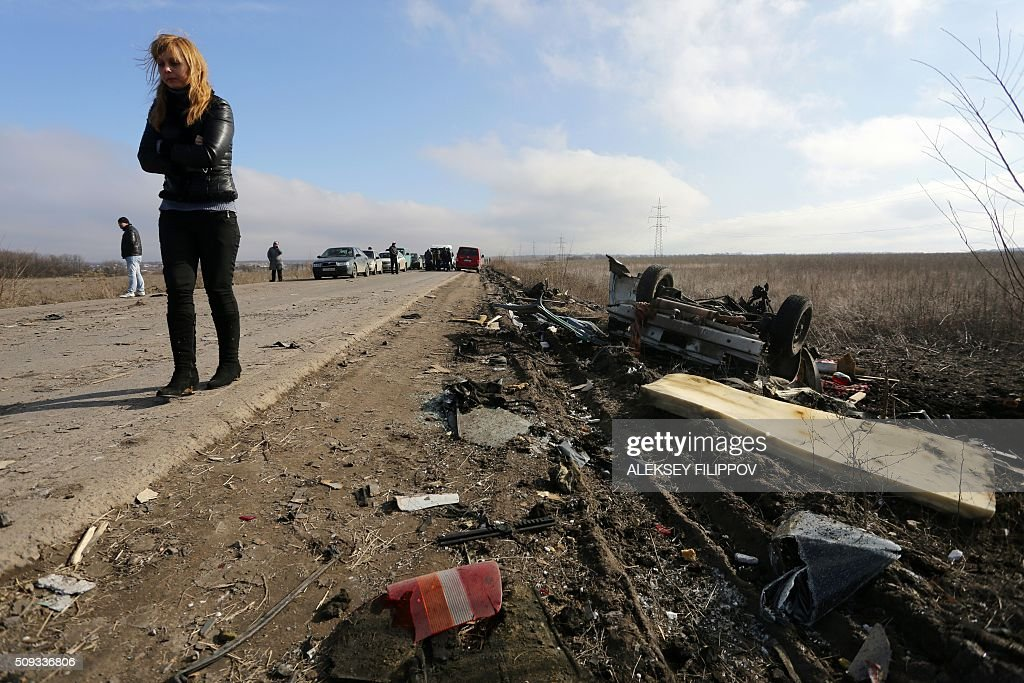 People look at the debris of a passenger minibus after it hit a mine as they queue at a checkpoint to cross the demarcation line between territory controlled by pro-Russian separatists and Ukrainian territory near Marinka on February 10, 2016. Three people were killed on February 10 when a passenger minibus hit a mine in separatist eastern Ukraine during a relative calm in fighting in the 21-month war. / AFP / ALEKSEY FILIPPOV