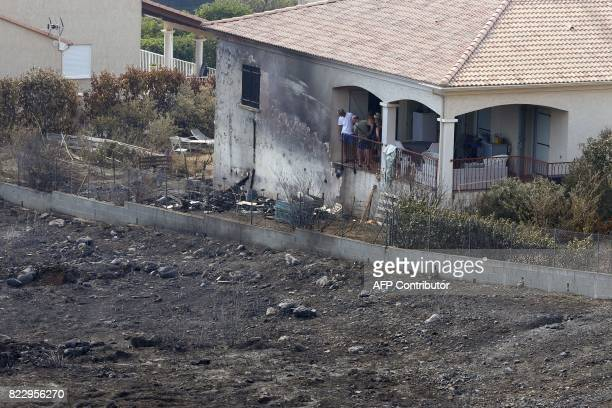 People look at the devastated land surrounding their house following a fire in Biguglia on the French Mediterranean island of Corsica on July 26 2017...