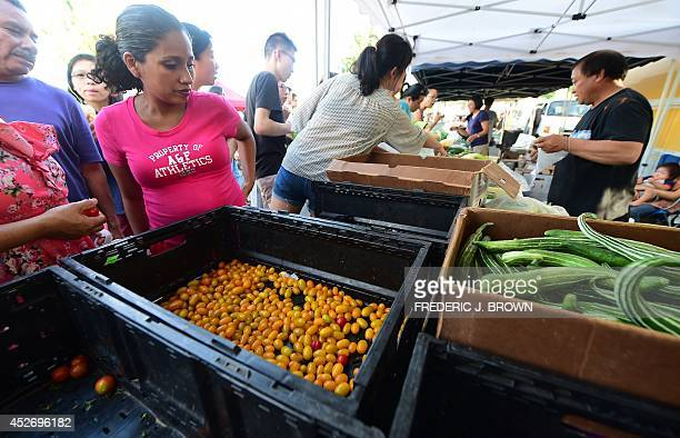 People look at the dwindling supply of yellow cherry tomatoes available at Monterey Park's Friday evening Farmers Market in Monterey Park California...