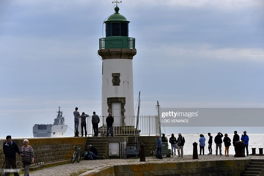 People look at the Egyptian Gamal Abdl Nasser (ex-Vladivostok) Mistral class ship as it leaves the harbour for a one week training session on May 6, 2016 in Saint-Nazaire, western France. The 'Nasser', first one of the two Mistral class ships sold by France to Egypt after its first sale cancellation to Russia, leaves Saint-Nazaire (Loire-Atlantique) on Friday for a week of Egyptian crew training at sea. / AFP / LOIC
