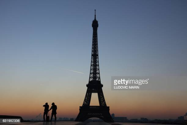 People look at the Eiffel tower at sunrise on January 18 2017 on the Place du Trocadero in Paris / AFP / LUDOVIC MARIN