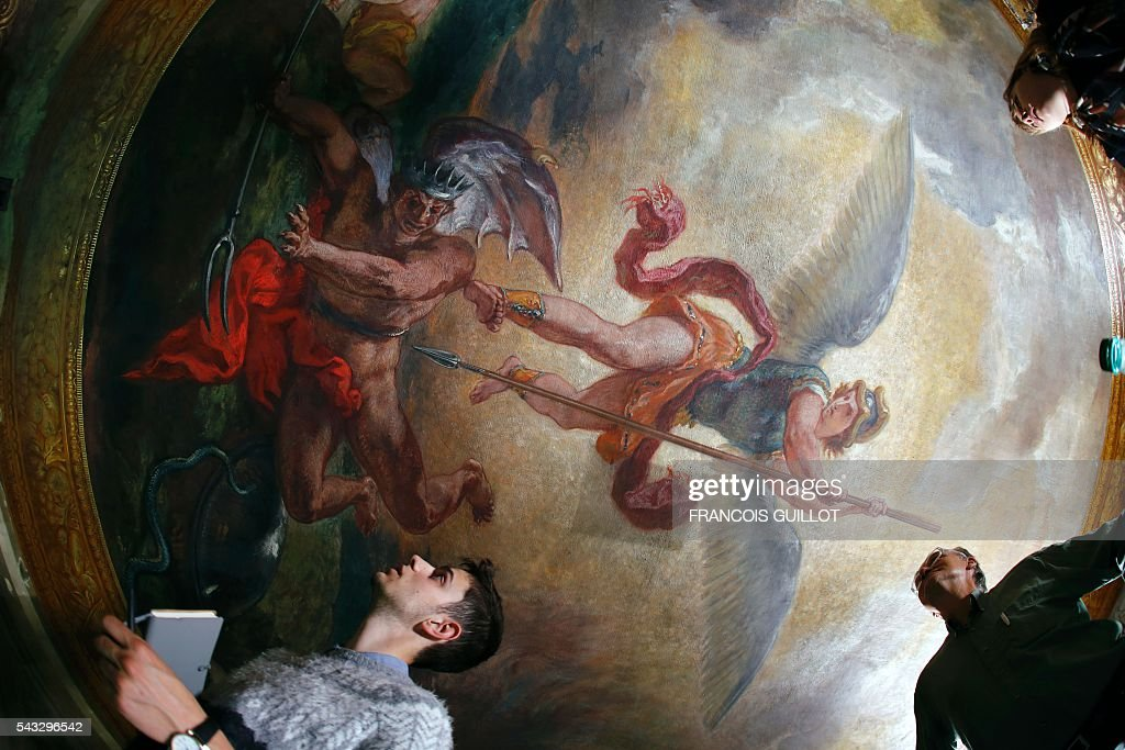 People look at the Eugene Delacroix paintings made between 1849 and 1861 during a restoration at the Saints-Anges chapel inside the Saint-Sulpice church in Paris, on June 27, 2016. / AFP / FRANCOIS