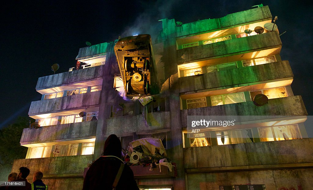 People look at the exterior of a bar made in the form of a block of flats with a London Underground train crashed into it on the first night of the Glastonbury Festival of Contemporary Performing Arts near Glastonbury, southwest England late on June 26, 2013. The festival attracts 170,000 party-goers to the dairy farm in Somerset, and this year's tickets sold out within two hours of going on sale. The Rolling Stones will perform at the festival for the first time, headlining on Saturday night.
