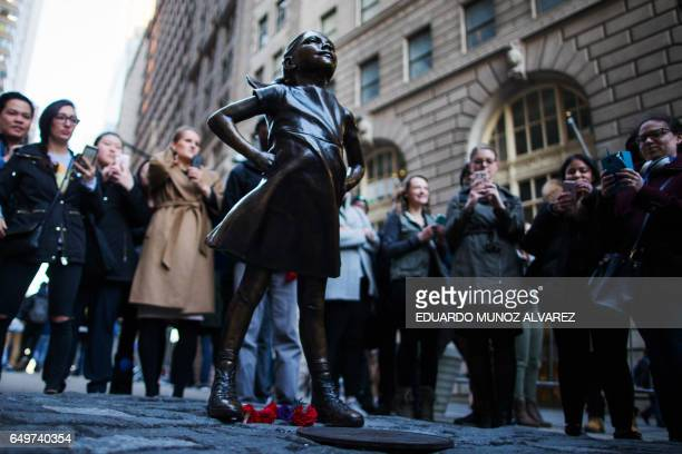 People look at 'The Fearless Girl' statue as it faces the iconic Wall Street charging bull statue as part of a campaign to push companies to add...