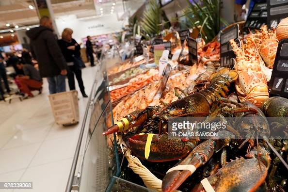 People look at the fresh fish and crustacean section of an hypermarket store of French retail giant Carrefour in VilleneuvelaGarenne near Paris on...