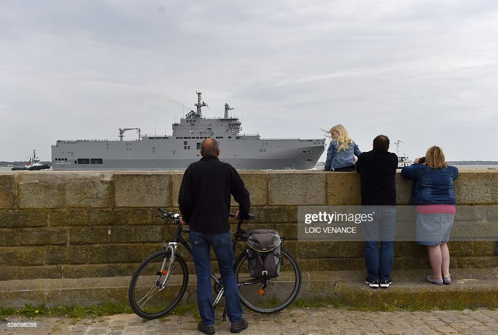 People look at the Gamal Abdl Nasser (ex-Vladivostok) Mistral class ship as it leaves the harbour for a one week training session on May 6, 2016 in Saint-Nazaire, western France. The 'Nasser', first one of the two Mistral class ships sold by France to Egypt after its first sale cancellation to Russia, leaves Saint-Nazaire (Loire-Atlantique) on Friday for a week of Egyptian crew training at sea. / AFP / LOIC