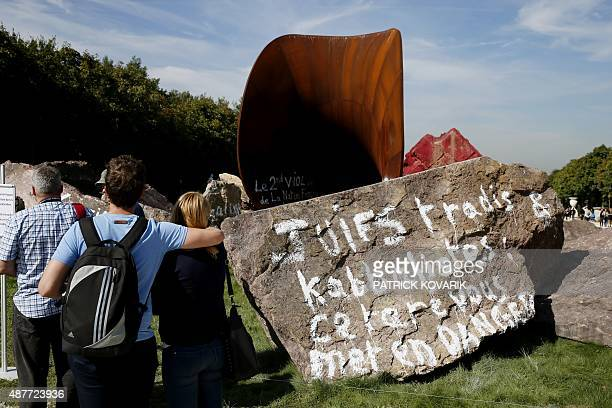 People look at the grafitti inscribed artwork by BritishIndian artist Anish Kapoor entitled 'Dirty Corner' in the gardens of the Chateau de...