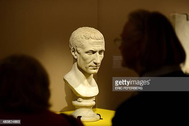 People look at the head of a statue depicting Julius Caesar as they visit the the exhibition entitled 'the myth of Cleopatra' on April 9 2014 at the...