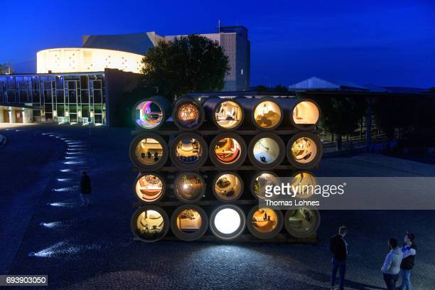 People look at the illumenated installation 'When We Were Exhaling Images' by the artist Hiwa K at night on June 8 2017 in Kassel Germany The...
