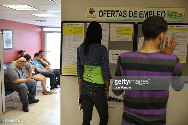 People look at the job listing posted on the wall at an unemployment office a day after the governor gave a televised speech regarding the...