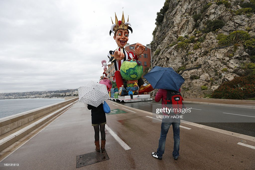 People look at the King and the Queen figures which are moved to hangar on March 5, 2013 in Nice, southeastern France due to bad weather conditions annonced on the French Rivieria tonight. The Carnival, which ends on March 6, 2013, celebrates the 'King of the five continents', marking the 140th anniversary of the French Riviera Nice carnival.