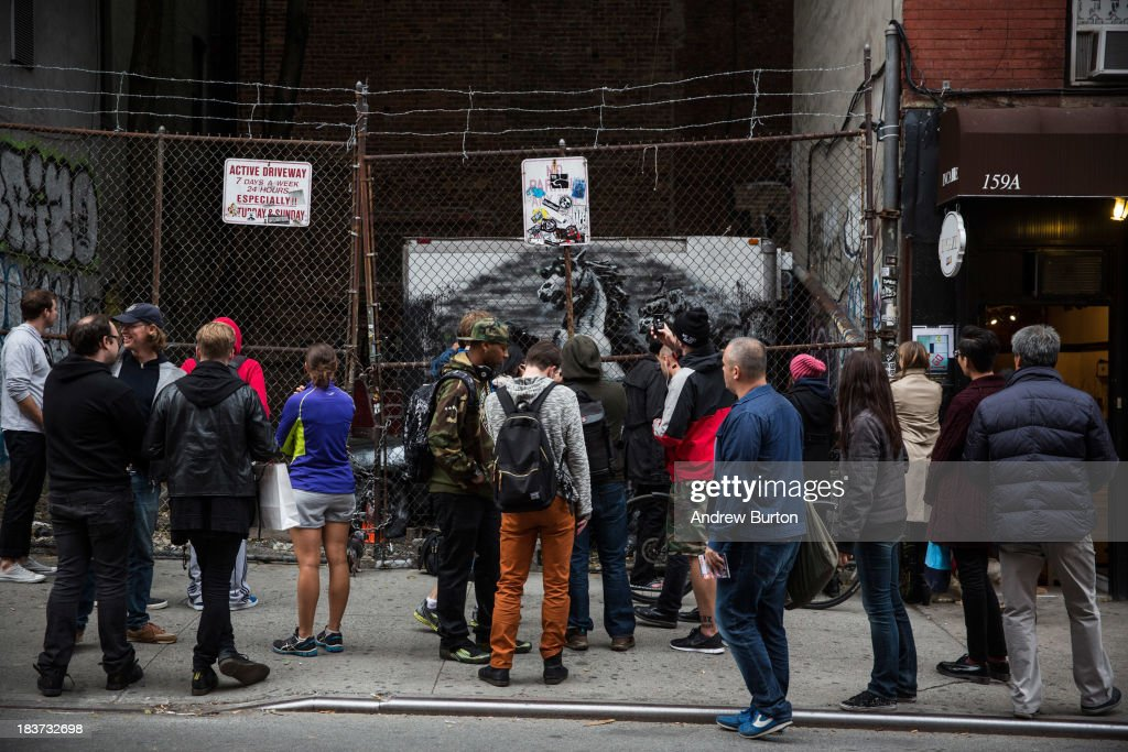 People look at the latest work from street artist Banksy on October 9, 2013 in the Lower East Side neighborhood of New York City. Banksy is in the midst of creating a month long series of pieces of street art.