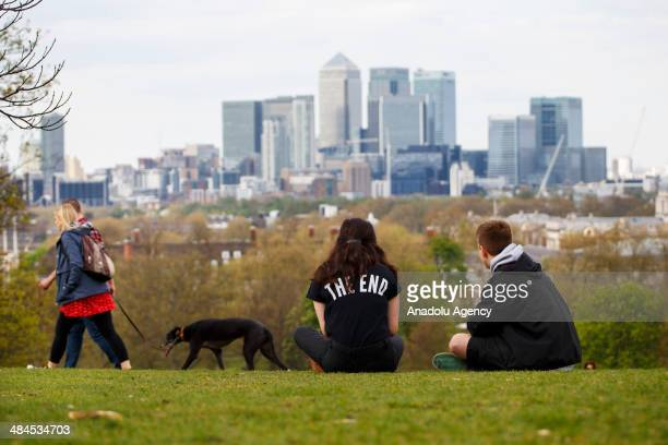 People look at the London skyline during a sunny weather at Greenwich Park in London on April 11 2014 as temperature hits 17C at weekend and...