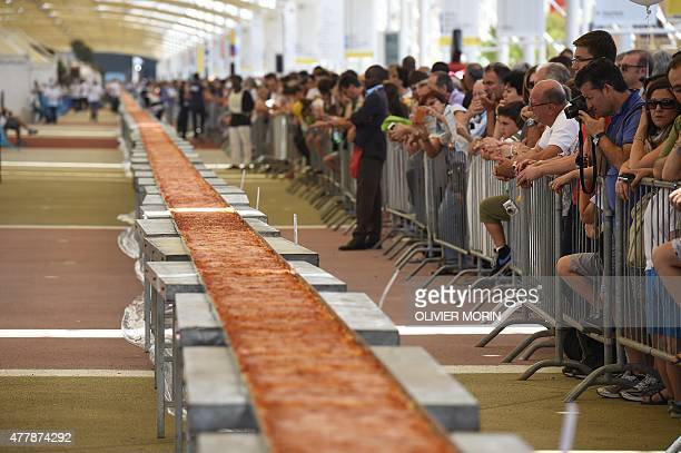 People look at the longest pizza in the world with 1600m long a new World Guinness Record on June 20 2015 in Milan at the Expo Milano 2015 AFP PHOTO...