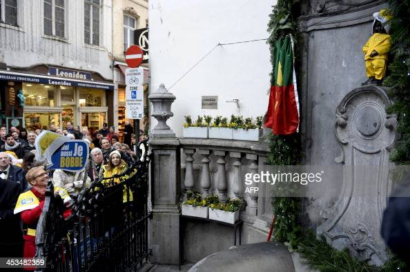 People look at the Manneken Pis dressed as a yellow Santa Claus on December 4 2013 in Brussels during the presentation of the 20132014 Bobalcohol...