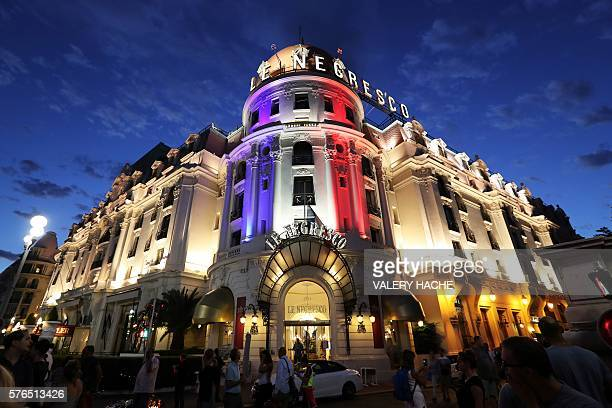 People look at the Negresco Palace illuminated with the colours of the French National flag in tribute for the victims of the deadly Bastille Day...